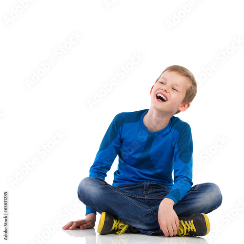 Laughing young boy sitting on the floor.
