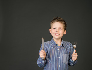 Cute boy with fork and knife. Hungry child.