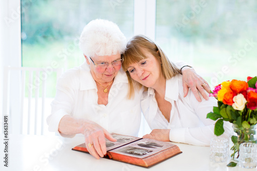 Beautiful woman and her loving mother watching photo album