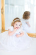 Adorable toddler girl in a beautiful white dress