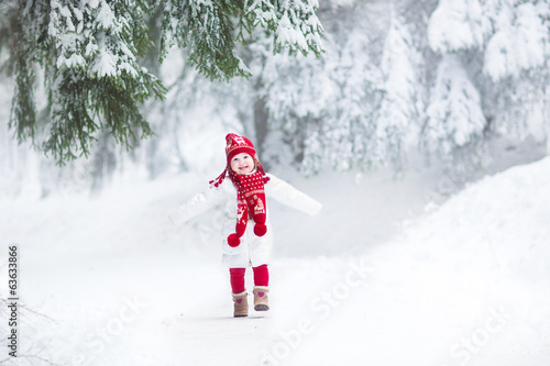 Funny laughing toddler girl running in a beautiful snowy park