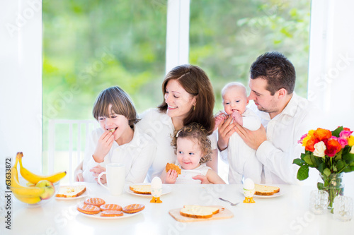 Happy young family with teenage boy, toddler girl, newborn son