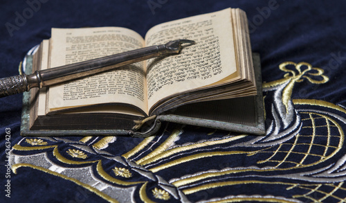 Open bible book in Hebrew with silver pointing hand