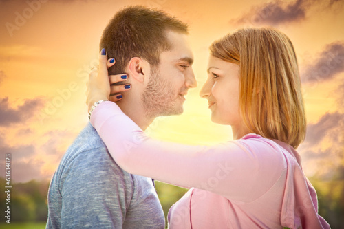 Beautiful young couple embracing on date in sunset