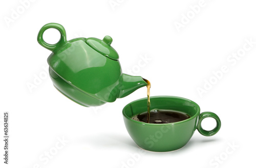 Green teapot pouring tea into a green cup
