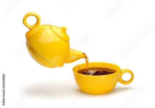 Yellow teapot pouring tea into a yellow cup