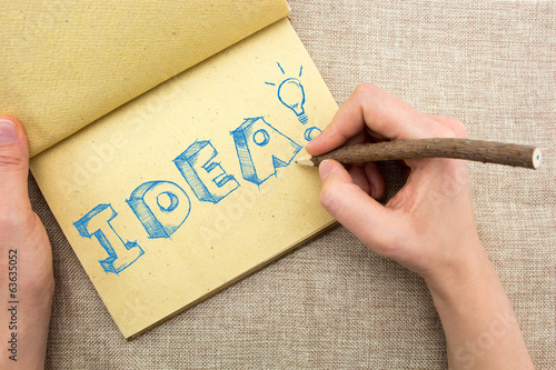 Notepad with hand drawing sketchy Idea word with light bulb