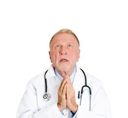 Senior male doctor praying asking for best patient outcome