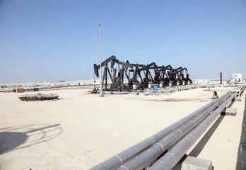 Black oil pump jacks in the desert of Bahrain, Middle East