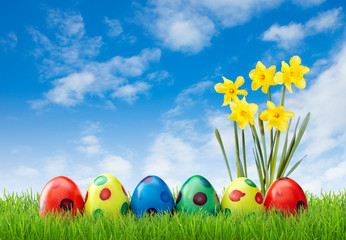 Spotted easter eggs in grass with flowers