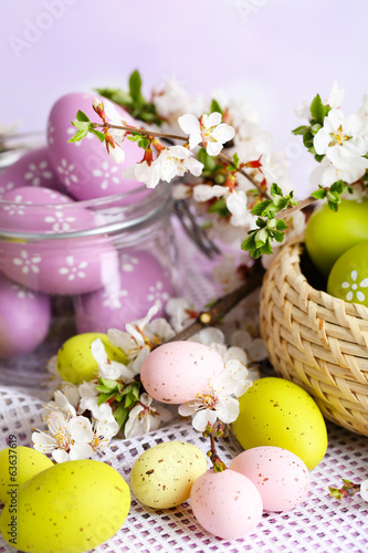 Composition with Easter eggs in glass jar and wicker basket,