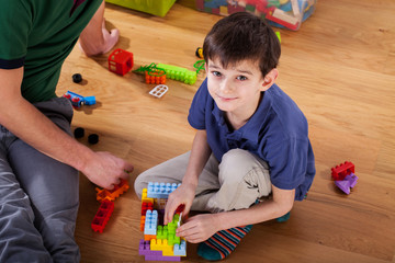 A boy with blocks on the floor