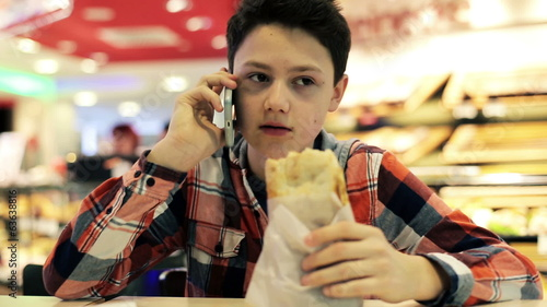 Young teenager talking on cellphone and eating sandwich