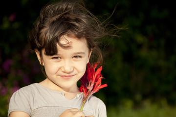 Niña sosteniendo flores rojas