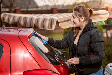 portrait of brunette woman washing red car outdoor
