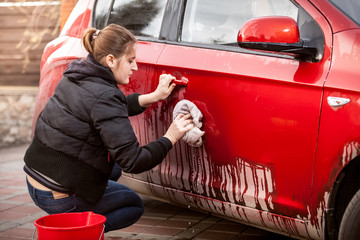 woman cleaning car door from mud and dirt