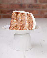 A piece of pecan cake with white buttercream icing