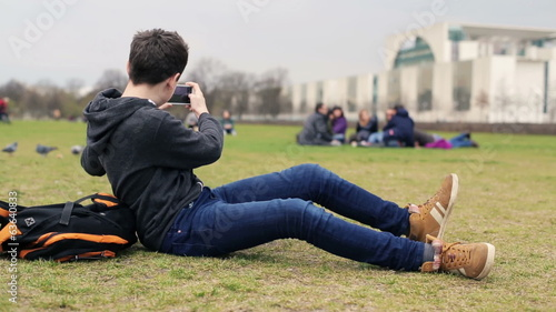 Young teenager taking photo with his smartphone in the park