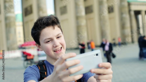 Young teenager taking selfie photo with his smartphone by Brande