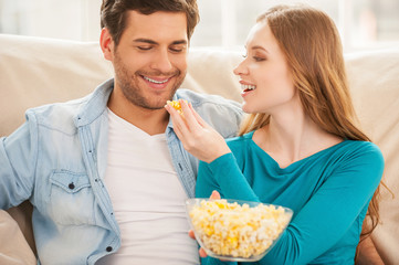 Couple eating popcorn.