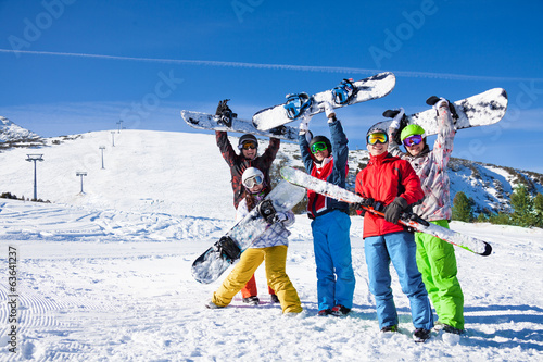 Foto op Canvas Wintersporten Five snowboarders holding oards and skies together