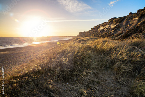 Landscape vivid sunset over beach and cliffs with added lens fla