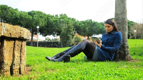 Beautiful woman working in park with tablet dolly shot