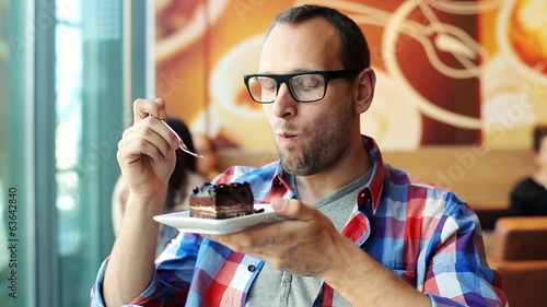 Happy young man eating tasty cake in cafe
