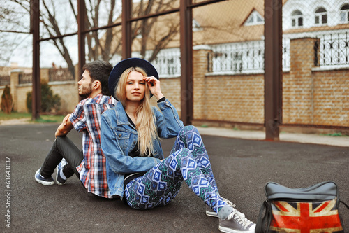 Young sensual romantic couple sitting on the ground
