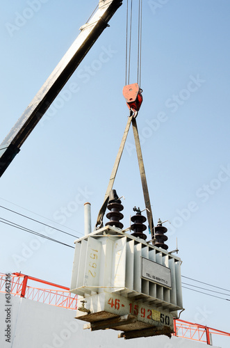 Crane hook lifts up distribution transformer