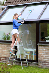 Young woman cleaning the outside windows of the house