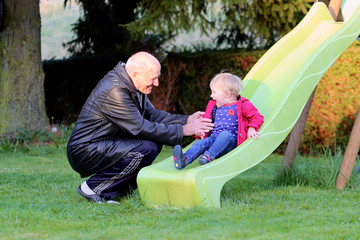 Happy grandfather plays with his granddaughter on the slide