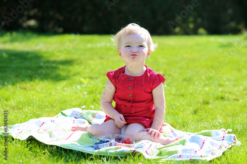 Adorable little girl eating berries in the garden