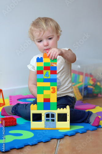 Happy toddler girl playing indoors with plastic blocks