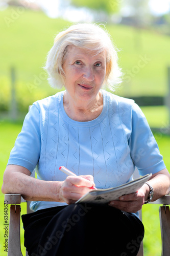 Happy senior woman reading newspaper sitting in the garden