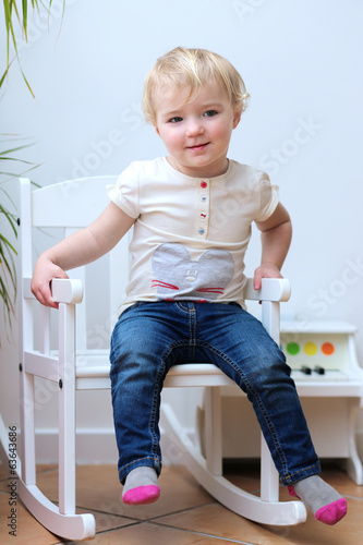 Portrait of beautiful toddler girl sitting on rocking chair