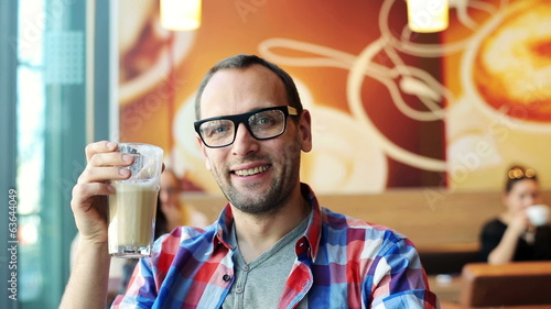 Happy young cheerful man sitting in cafe
