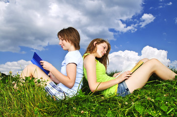 Two girls reading outdoors in summer