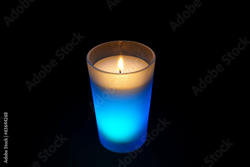 burning light blue candle isolated on black background