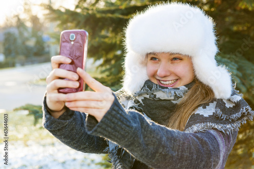 Young girl using cell phone in winter