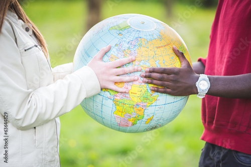 Multiracial Teen Couple Holding Globe Map