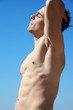 Man with perfect body with closed eyes in front of sky