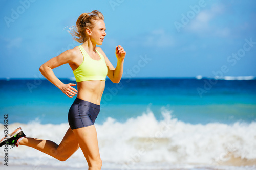 Athletic Young Woman Running on the Beach