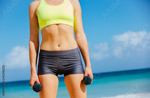 Close-up of torso of fitness woman holding barbells - 63646258