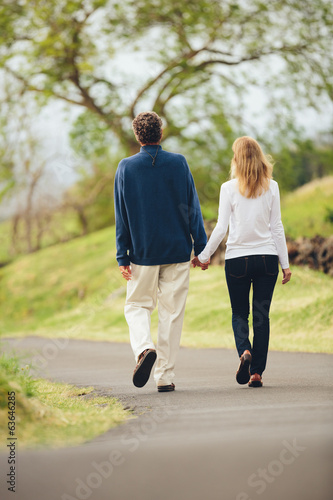 Happy loving middle aged couple walking