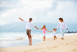 Happy young family walking on the beach