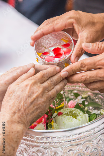 Pour water on the hands of revered elders and gives blessing in