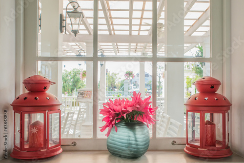 Jug of fresh summer flowers and lamps on a window sill