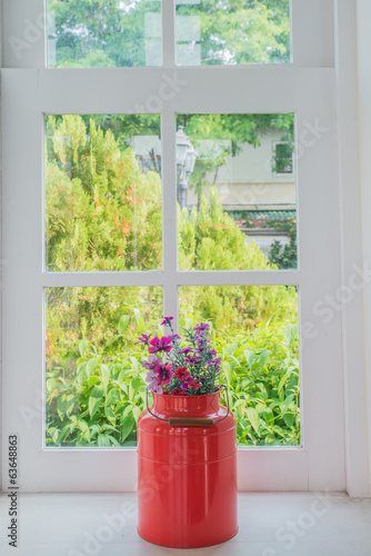 Jug of fresh summer flowers on a window sill