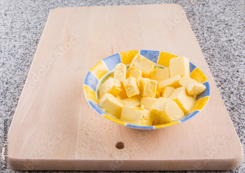 A group of melting butter in a bowl on a pastry board